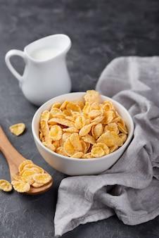 Flocos de milho no café da manhã em uma tigela com colher de pau e leite
