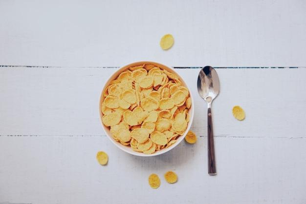 Flocos de milho pequeno-almoço na tigela e colher - comida saudável cereal