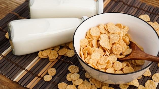 Flocos de milho saudáveis, leite e uma colher de pau em um guardanapo de bambu. garrafas de vidro com leite para um café da manhã saudável