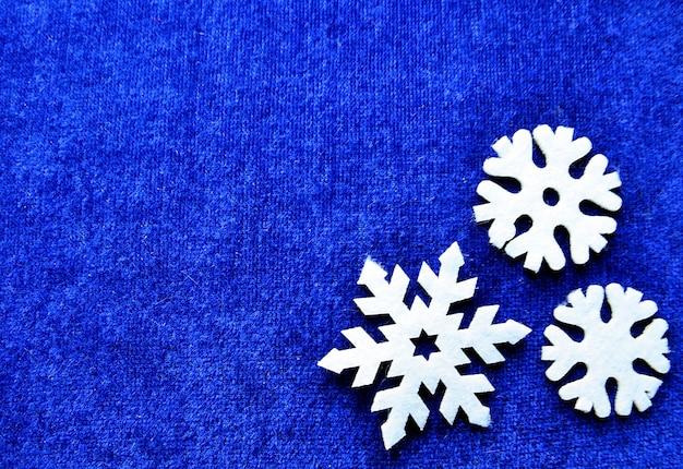 Flocos de neve brancos decorativos em fundo azul com espaço de cópia conceito de decoração de natal