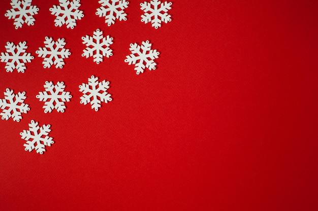 Flocos de neve brancos sobre fundo vermelho. foto horizontal de natal e ano novo