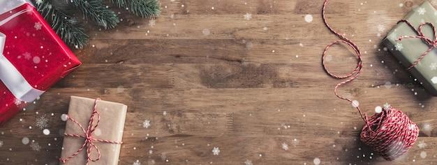 Flocos de neve caindo sobre caixas de presente em uma mesa de madeira - banner de natal com espaço de cópia