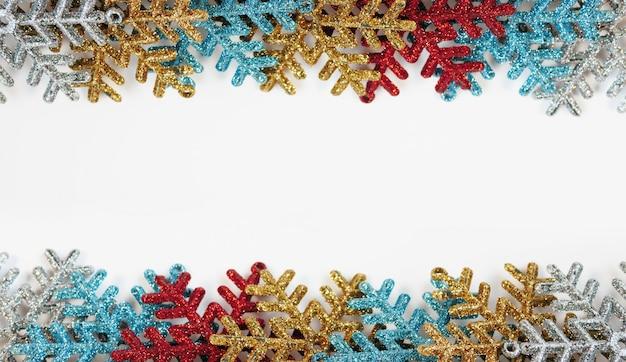 Flocos de neve coloridos sobre fundo branco, com espaço de cópia