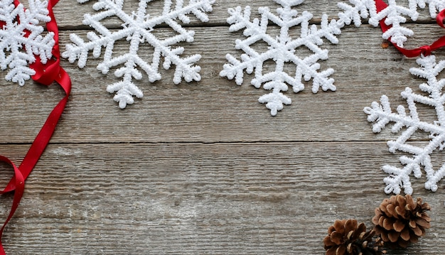 Flocos de neve com pinhas e fita vermelha