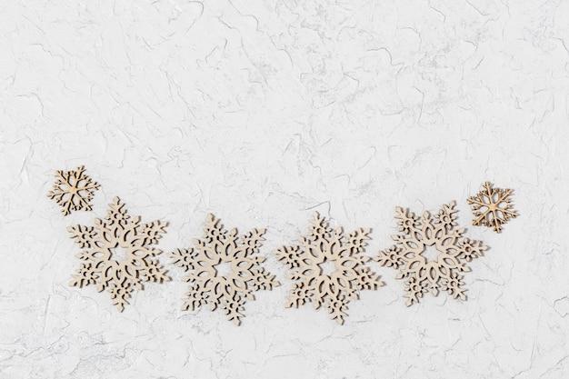 Flocos de neve de madeira pequenas decorações sobre fundo claro.
