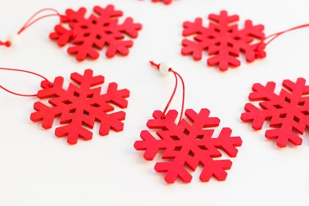 Flocos de neve de madeira vermelhos brilhantes sobre fundo branco. decorações de natal e ano novo. enfeite de inverno, decoração sazonal. vista do topo.