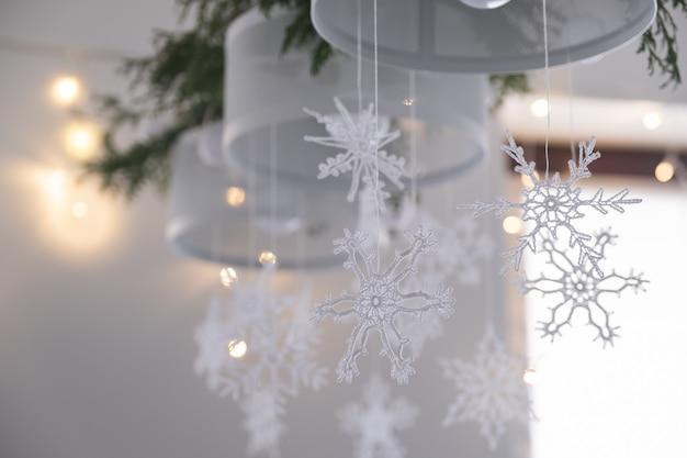 Flocos de neve de malha branca linda decoração de interiores de inverno pendurar em um lustre no natal.