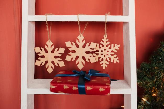 Flocos de neve de natal de madeira e caixa de presente com fita azul na escada na parede vermelha
