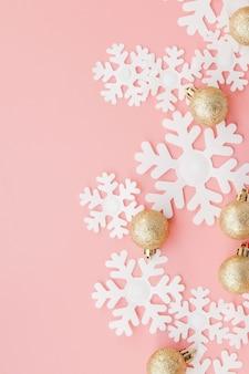 Flocos de neve de papel e bolas de ouro sobre fundo rosa