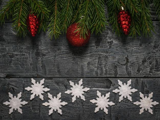 Flocos de neve de papel e ramos de abeto vermelho verde com brinquedos em um fundo de madeira.