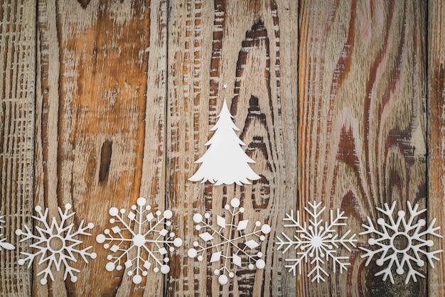 Flocos de neve de papel em fundo de madeira.