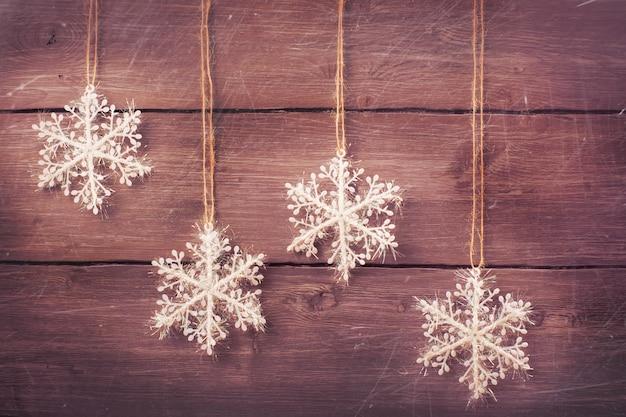 Flocos de neve de prata do white christmas sobre o fundo de madeira do vintage. imagem enfraquecida