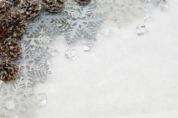 Flocos de neve de prata e flocos de neve e cones de pinheiro aninhados no gelo