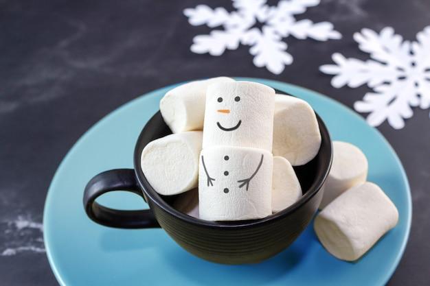 Flocos de neve do boneco de neve de natal e marshmallows na xícara