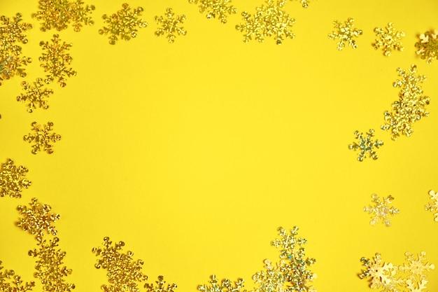 Flocos de neve dourados na superfície amarela