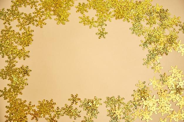 Flocos de neve dourados na superfície bege