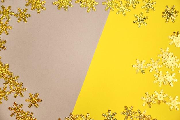 Flocos de neve dourados na superfície cinza e amarela