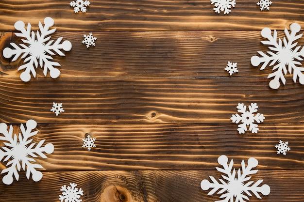 Flocos de neve fofos de inverno em fundo de madeira.