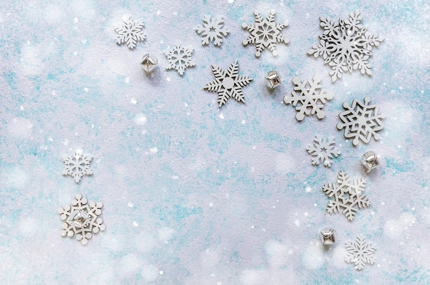Flocos de neve grandes e pequenos em fundo azul turquesa. plano de fundo abstrato de natal e ano novo. espaço para texto. foco suave. vista do topo.