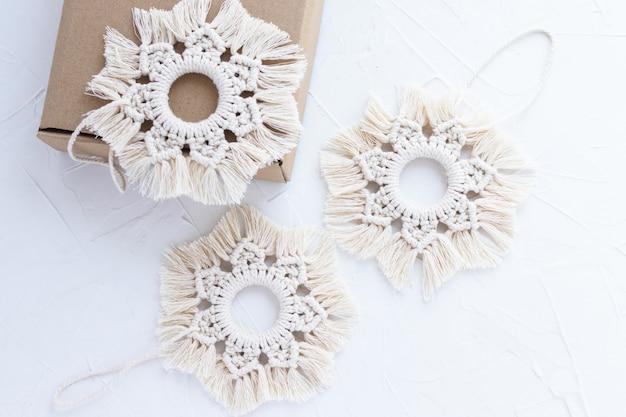 Flocos de neve na técnica de macramê em fundo de massa branca. caixa de papelão artesanal. decoração artesanal para árvore de natal. ano novo, inverno, decoração sazonal.