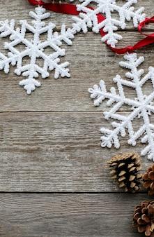 Flocos de neve, pinhas e fita vermelha