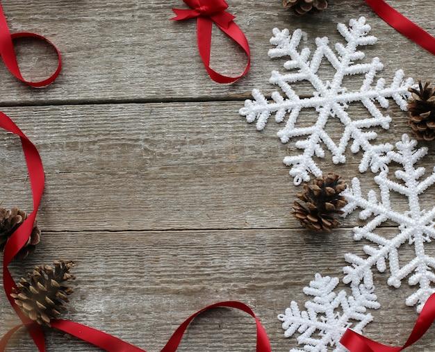 Flocos de neve, pinhas e fitas vermelhas