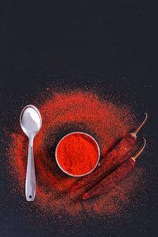 Flocos de pimenta vermelha e pó de pimentão estouraram em backgroundv preto
