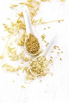 Flocos e grãos de aveia em duas colheres, hastes de aveia no fundo de placas de madeira claras de cima