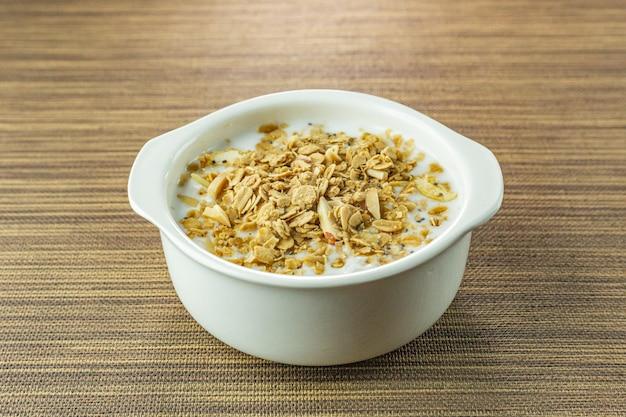 Flocos e leite da amêndoa do alimento da manhã na bacia branca na tabela de madeira.