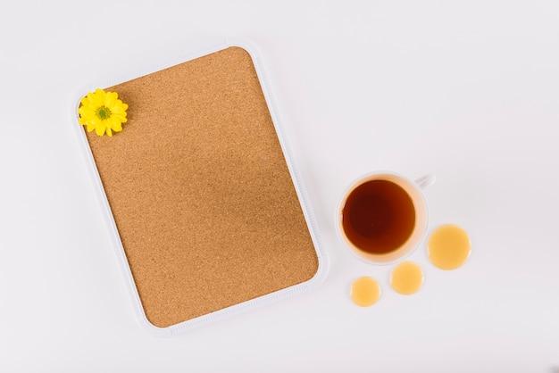 Flor amarela no quadro de cortiça perto de chá e mel cai sobre a superfície branca