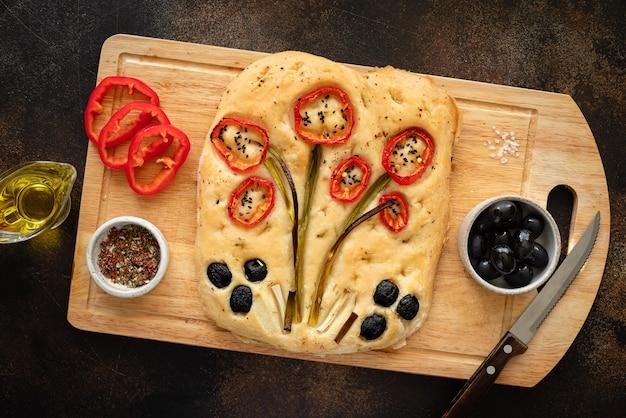 Flor art focaccia com vegetais e ervas em uma tábua de madeira com ingredientes da comida italiana