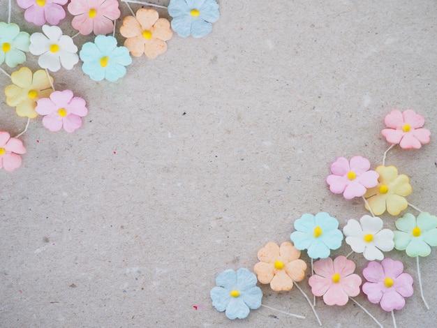 Flor artificial pastel colorida no fundo de papel reciclado, decoração floral do cartão