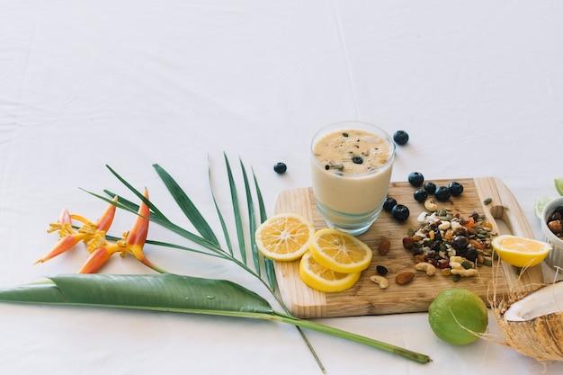 Flor ave do paraíso; smoothie com dryfruits e frutas cítricas em fundo branco