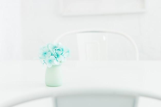 Flor azul da hortênsia no vaso cerâmico em cima da mesa na bela sala branca.