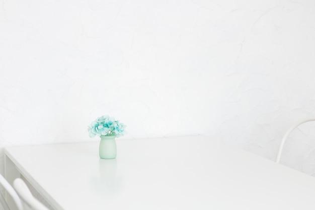 Flor azul da hortênsia no vaso cerâmico na tabela na sala branca bonita.