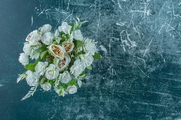 Flor branca artificial em um vaso, no fundo azul.