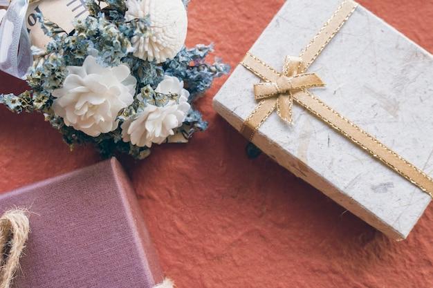 Flor branca com caixa de presente em fundo vermelho
