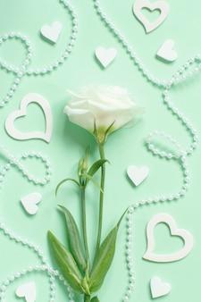 Flor branca com pérolas e corações ao redor em uma vista superior verde-clara
