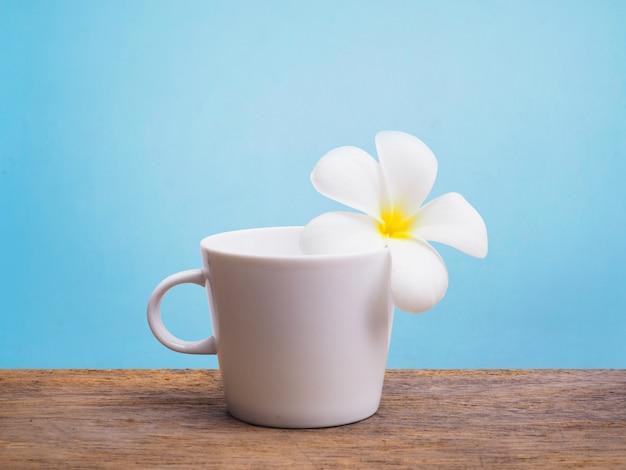 Flor branca de plumeria e copo vazio de café