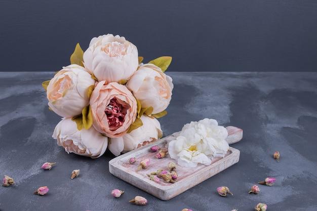 Flor branca, sementes de flores e buquê na superfície azul.