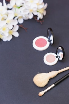 Flor buquê branco; pincel de blush e maquiagem em fundo cinza