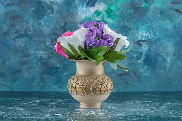 Flor colorida artificial em um vaso, no fundo azul.