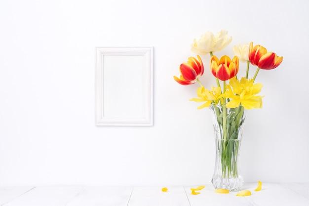 Flor da tulipa em um vaso de vidro com moldura para retrato no fundo da mesa de madeira branca contra a parede limpa em casa, close-up, conceito de decoração do dia das mães.
