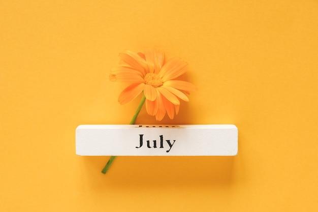 Flor de calêndula laranja e calendário mês de verão julho