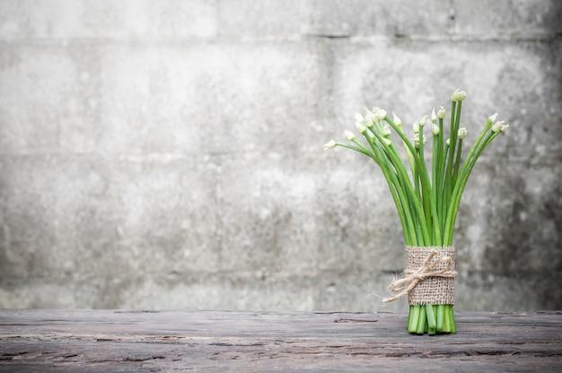 Flor de cebolinha ou cebolinho chinês na mesa de madeira com fundo de parede de tijolo antigo