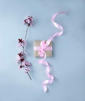 Flor de cerejeira e caixa de presente com fita rosa na parede cinza claro
