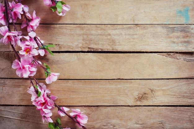 Flor de cerejeira e flores artificiais no fundo de madeira do vintage com espaço da cópia.