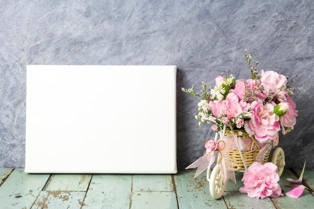 Flor de cravo-de-rosa na bicicleta e moldura de tela em branco na madeira vintage
