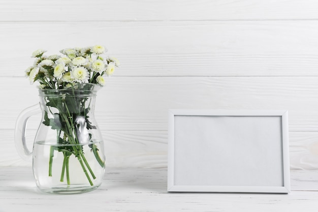 Flor de crisântemo no jarro de vidro contra o quadro em branco no pano de fundo de madeira