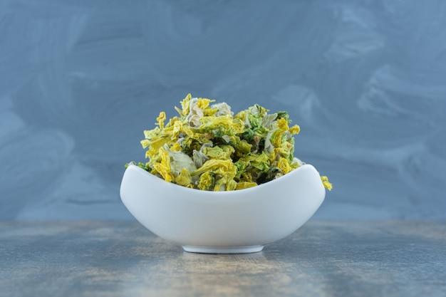 Flor de crisântemo seco em tigela branca.